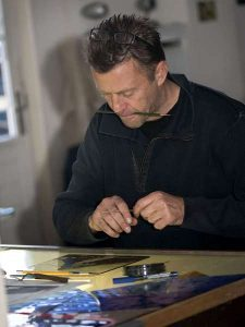 Afbeelding van ruud harberts aan het brandschilderen in het glasatelier