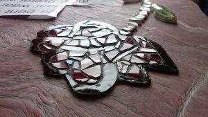 Afbeelding van een roos van glas in mozaiek op natuursteen als detail van een grafmonument | door glasatelier ruud harberts